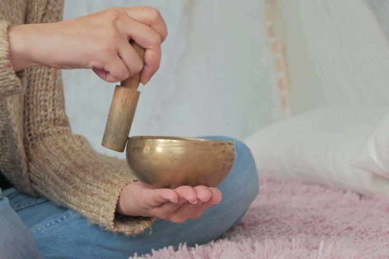 Jeune femme en cardigan se relaxant avec un bol chantant tibétain.