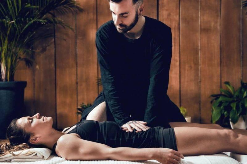 Belle jeune femme sportive profitant d'un massage shiatsu, allongé sur le sol, portant des vêtements noirs, fond en bois