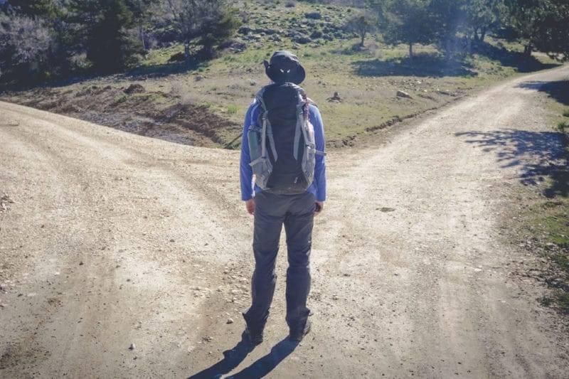 Homme choisissant sa direction sur un chemin de terre
