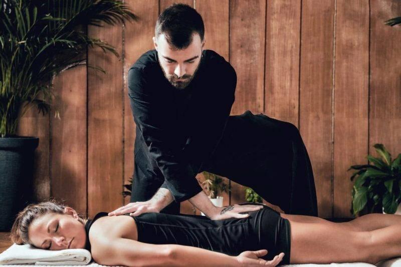 Thérapeute shiatsu pratiquant un massage à une femme sportive allongée sur le ventre.