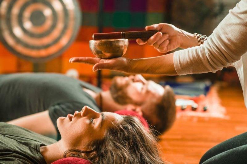 Une femme et un homme sont allongés et écoutent un bol tibétain comme un mantra