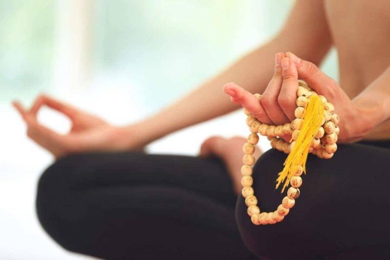 Femme méditant en utilisant un mala de méditation