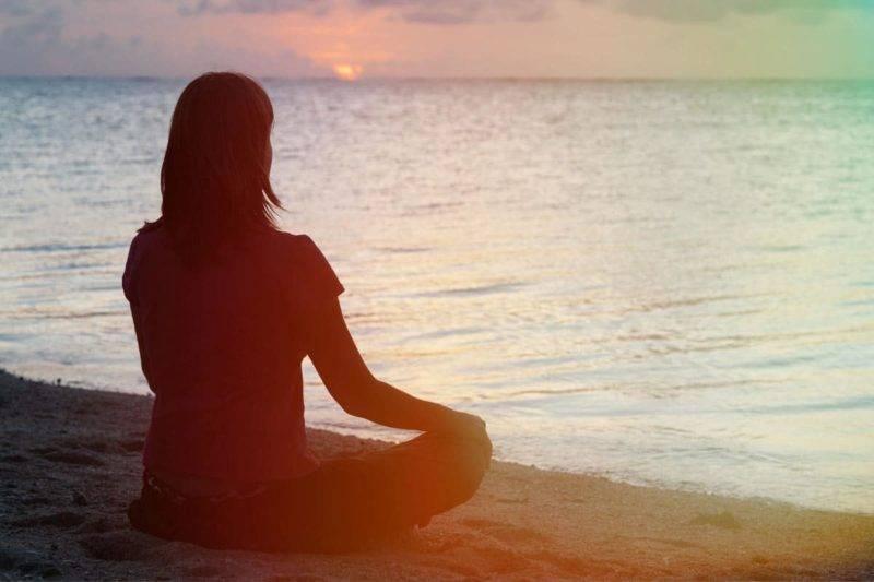 Jeune femme en pleine méditation sur le coucher du soleil sur une plage tropicale
