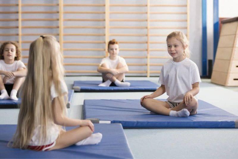 jeunes filles heureuses assises face à face sur des tapis d'entraînement bleus avec les jambes croisées pendant les cours d'éducation physique à l'intérieur du gymnase