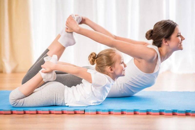 Mere et fille dans une position de yoga sur tapis bleu