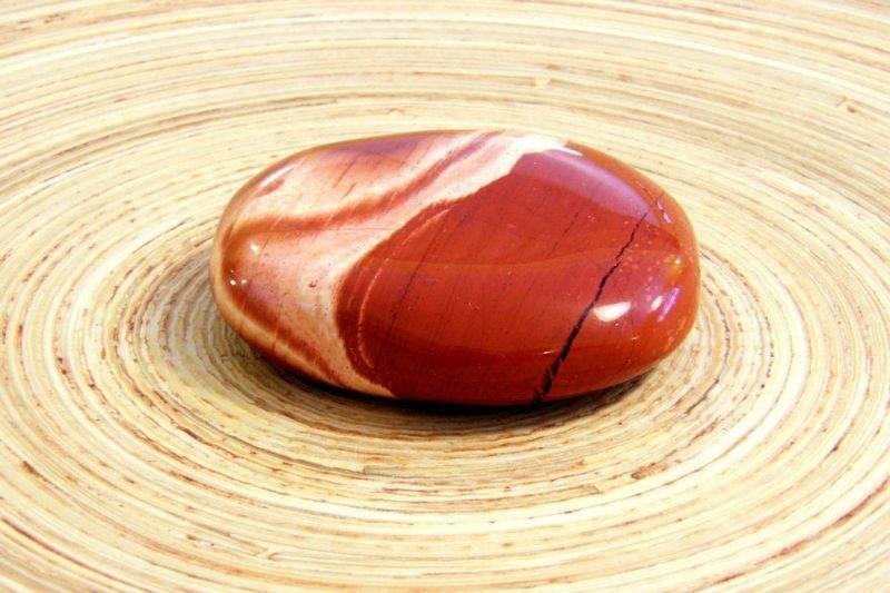 Pierre de jaspe rouge sur du bois naturel