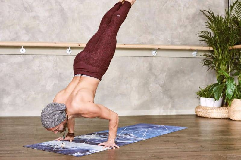 Homme musclé pratiquant du Yoga sur un beau tapis.