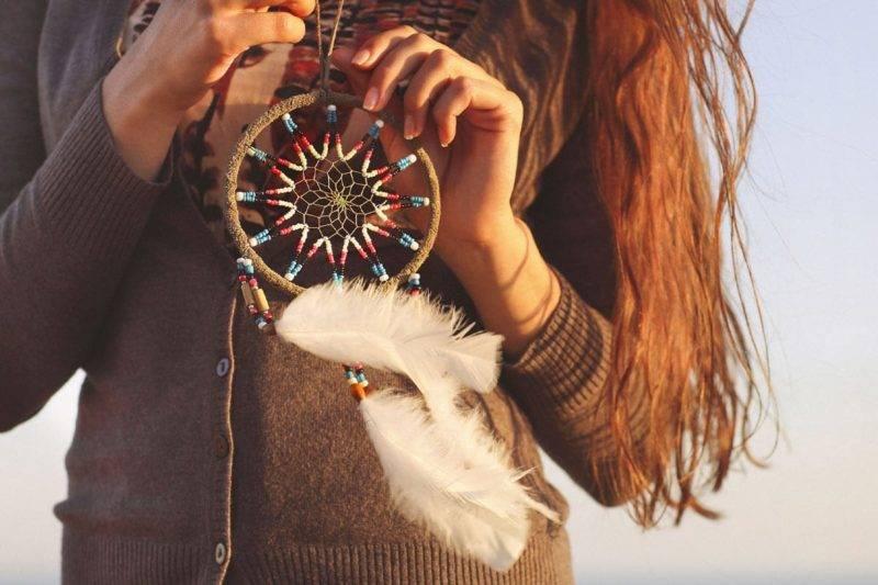 Femme brune tenant un attrape rêve entre ses mains