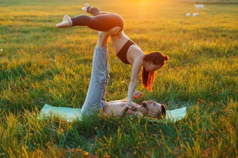Couple pratiquant le tantra yoga sous un couché de soleil dans l'herbe