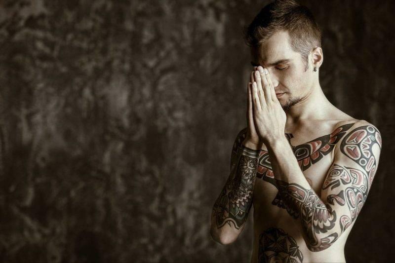 Homme tatoué pratiquant le tantra yoga