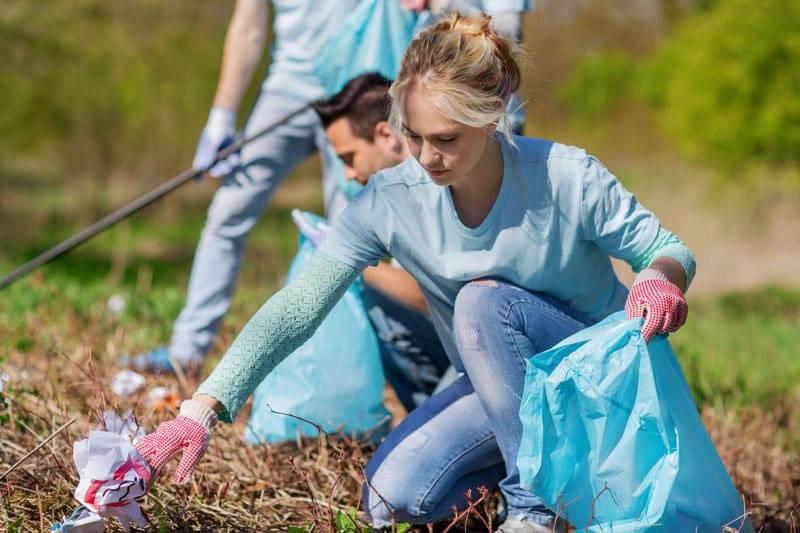 Femme ramassant des déchets dans un parc en bénévolat pour augmenter son karma.