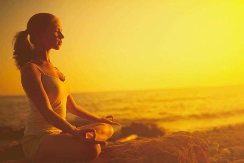 Une femme médite sur la plage en face de la mer