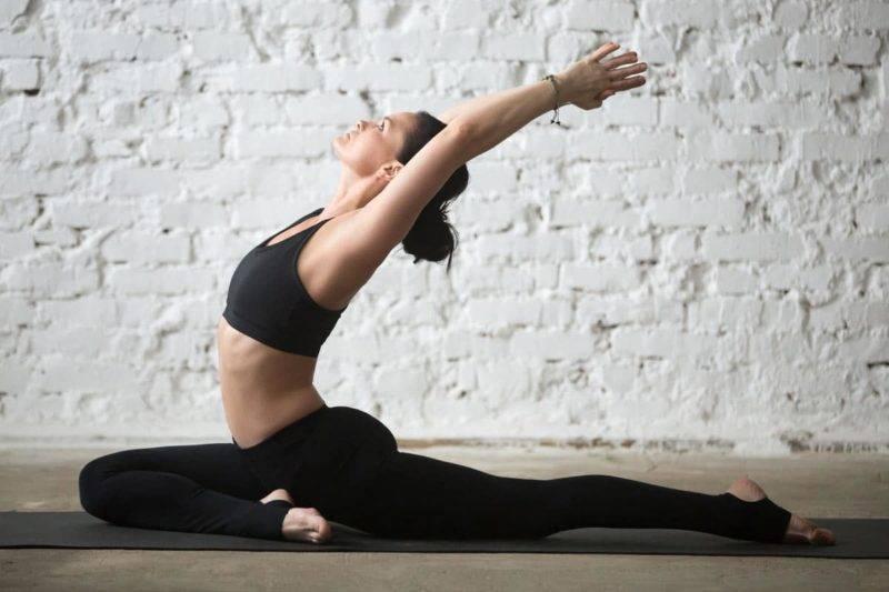 Femme pratiquant le yoga dans une variation du pigeon