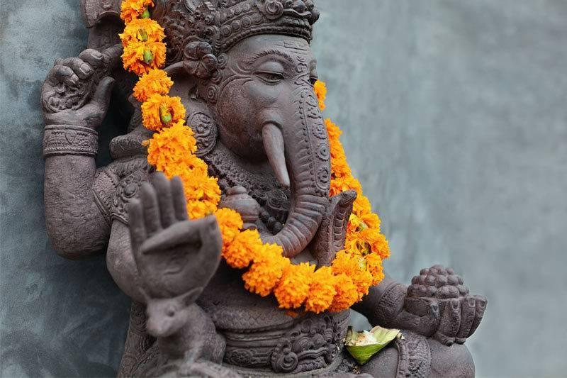 Ganesh avec des masques Barong balinais assis devant le temple