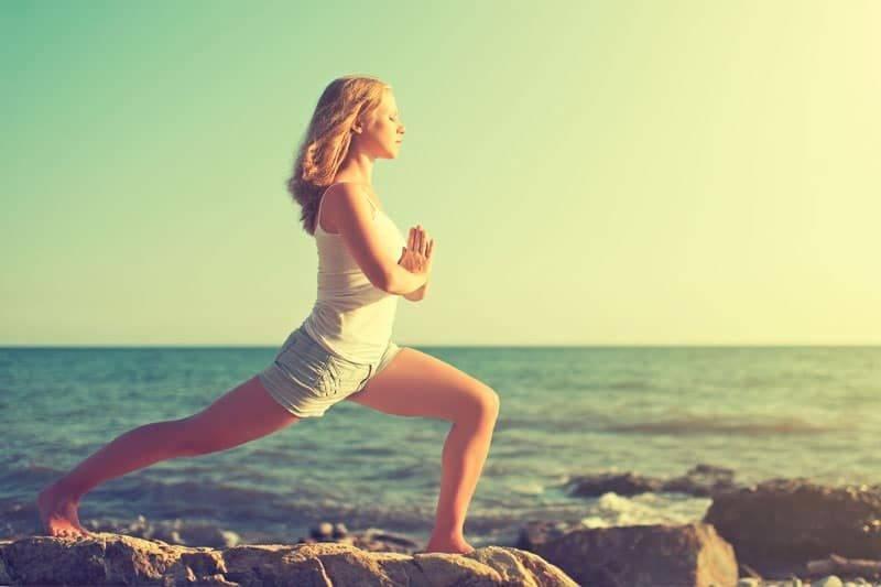 Jeune femme pratiquant du karma-yoga sur la côte de la mer sur la plage
