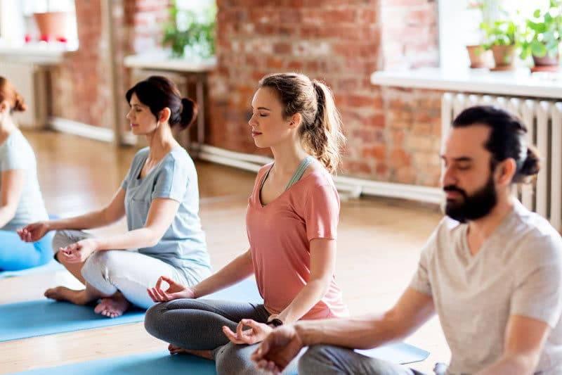 Groupe de personnes faisant des exercices de méditation dans un studio