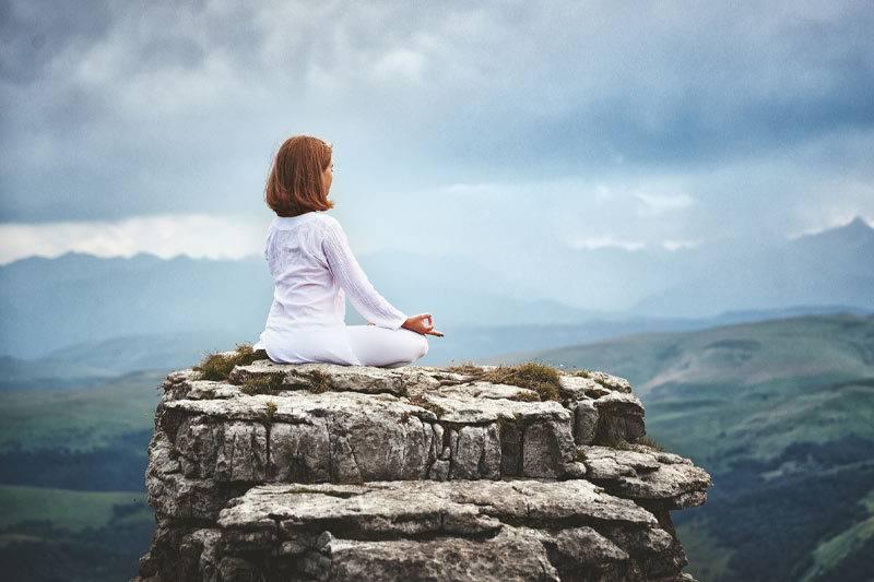 Femme qui médite en haut d'une montagne