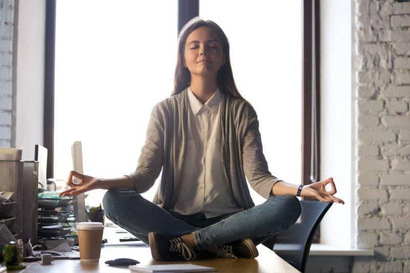 Femme méditant avec pierres de lithothérapie