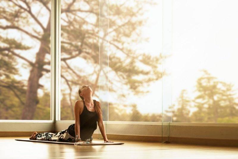 Femme sur tapis pratiquant le yoga en position du cobra pour ouvrir le chakra du cœur