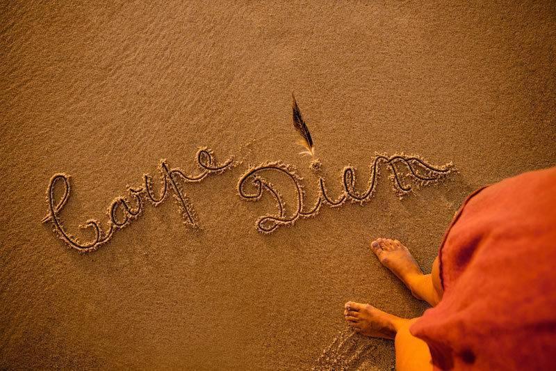 Femme sur la plage avec les mots Carpe Diem écrits dans le sable