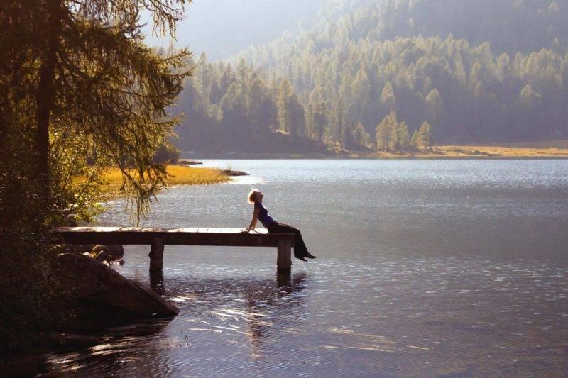 Une femme profite de la nature près d'un lac de montagne