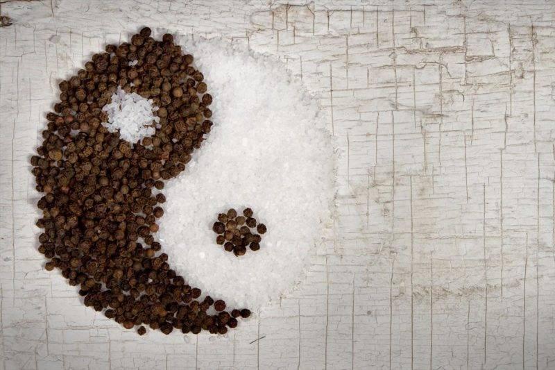 Yin et le Yang avec du poivre et du sel sur une vieille porte de fond