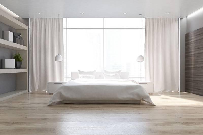 Chambre à coucher avec un plancher en bois, un lit double près d'une grande fenêtre et une bibliothèque sur la gauche.
