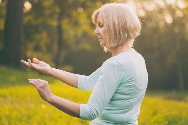 Femme agée pratiquant dans un parc le tai-chi