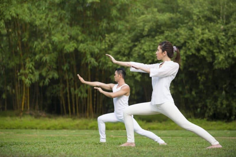 Homme asiatique et femme faisant du Tai Chi dans un jardin