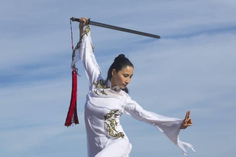 Jeune femme danseuse effectuant du qi gong avec une épée
