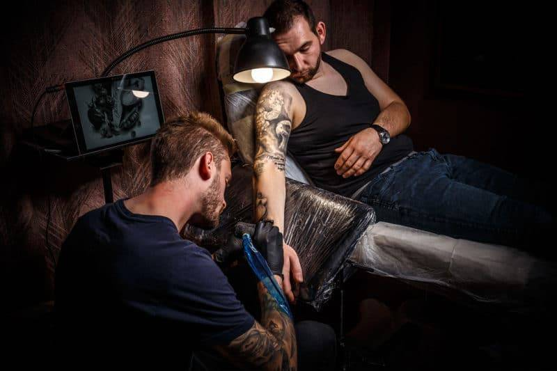 Tatoueur dans son salon qui tatoue une main de fatma