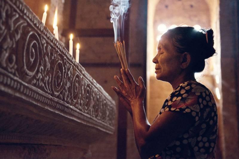 Femme asiatique traditionnelle faisant une prière avec des bâtons d'encens dans un temple