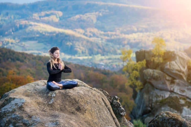 Femme qui médite sur une montagne les mains en prière