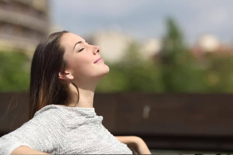 Jeune femme sur un banc qui profite du moment présent