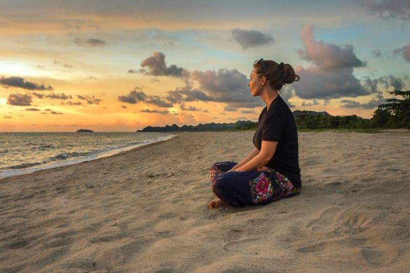 Femme qui médite sur une plage