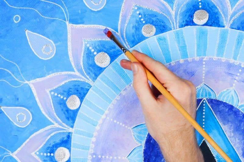 Main qui peint un mandala