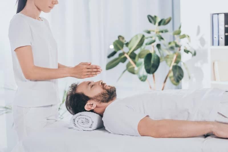 Homme recevant un traitement de reiki sur une table de massage