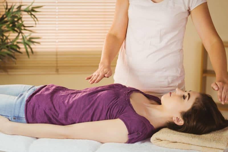 Jeune femme ayant un traitement reiki dans la salle de thérapie