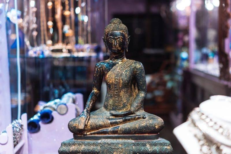 Statue de Bouddha devant une fenêtre