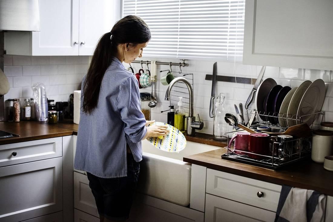 Jeune femme faisant la vaisselle et pratiquant la méditation en pleine conscience