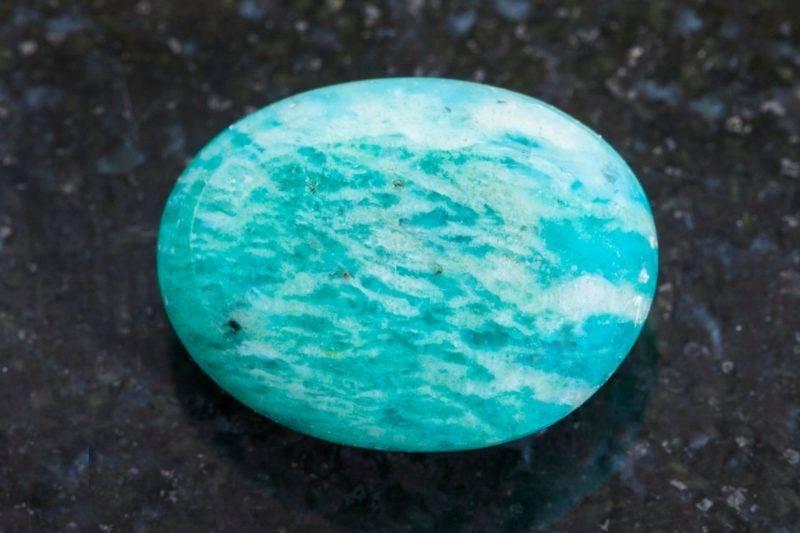 Pierre d'amazonite polie sur un fond en granit