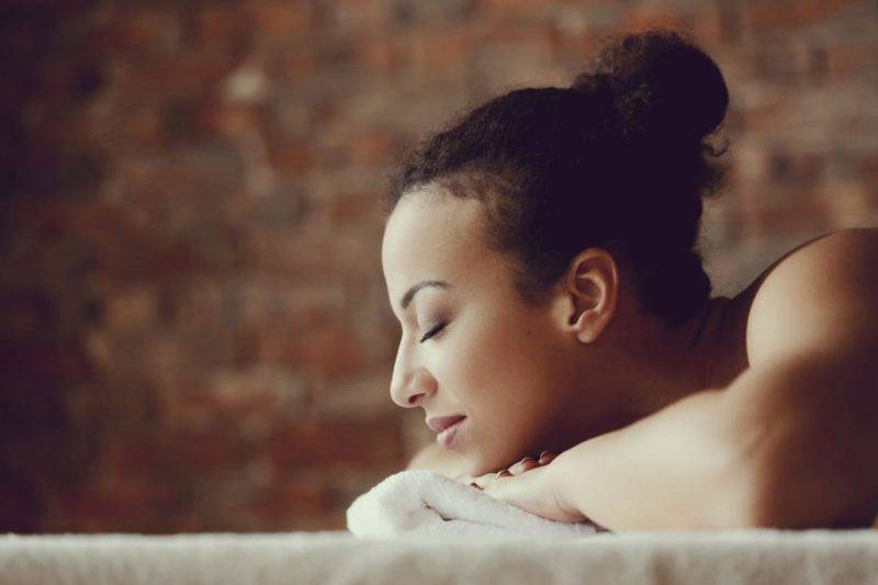 Femme allongé qui reçoit un massage