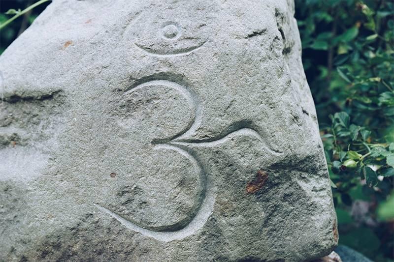 Symbole tibétain Om gravé sur une grosse pierre