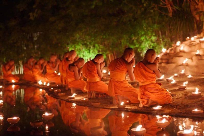 Moines assis qui méditent avec beaucoup de bougies dans le temple thaïlandais