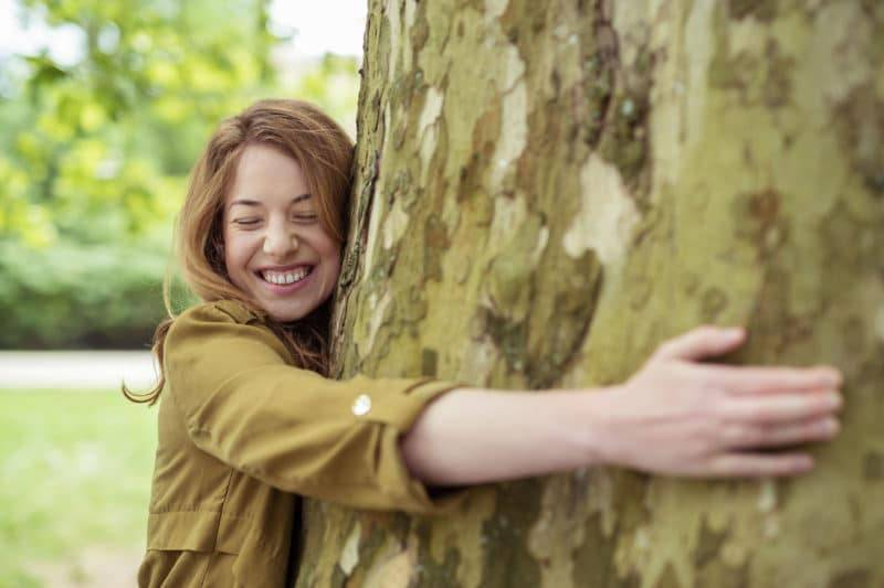 Femme qui fait un câlin à un arbre