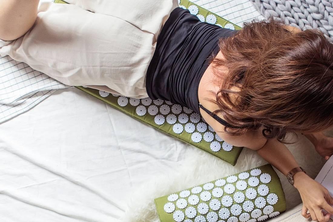 Jeune femme sur un tapis d'acupression
