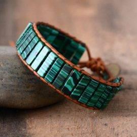 Bracelet Revitalisant en Malachite avec un fil brun posé sur une pierre