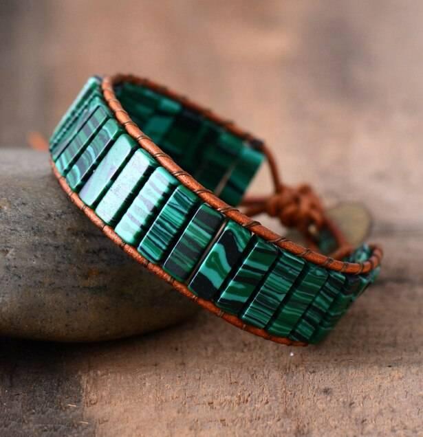 Bracelet Revitalisant Malachite avec un fil brun posé sur une pierre