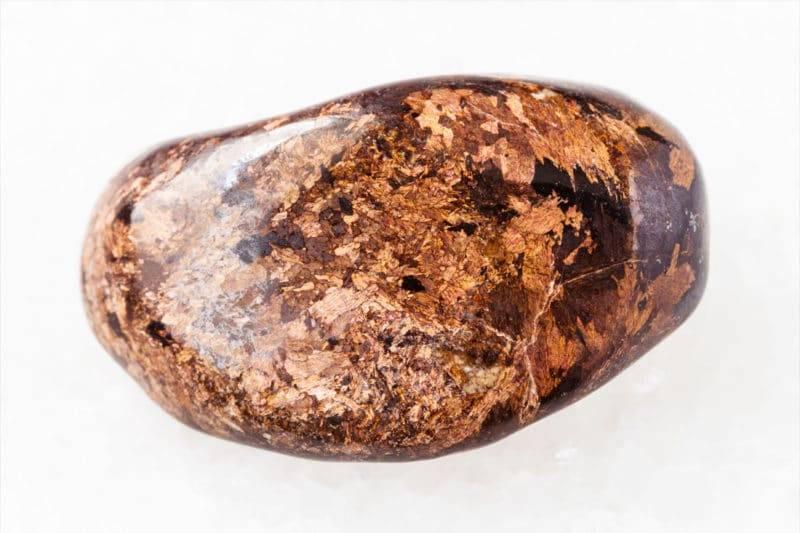 Pierre polie de bronzite sur fond blanc
