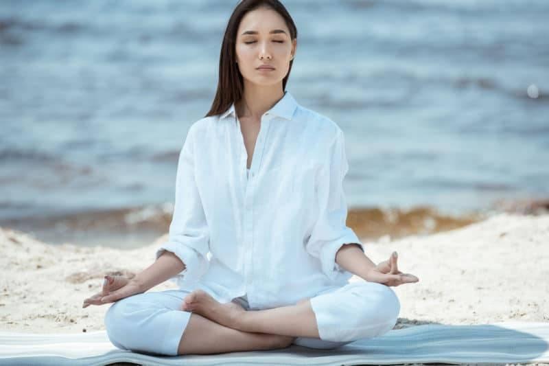 Jeune femme dans la position du demi lotus sur la plage